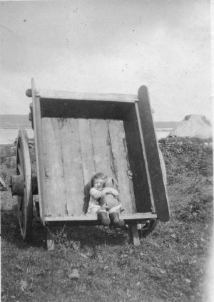 Peggy MacLean sitting in the peat cart, Vallay c.1940's