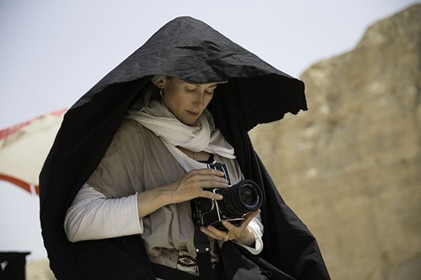 A white woman is adjusting a camera, wearing a large black hood of fabric which is billowing in the wind.