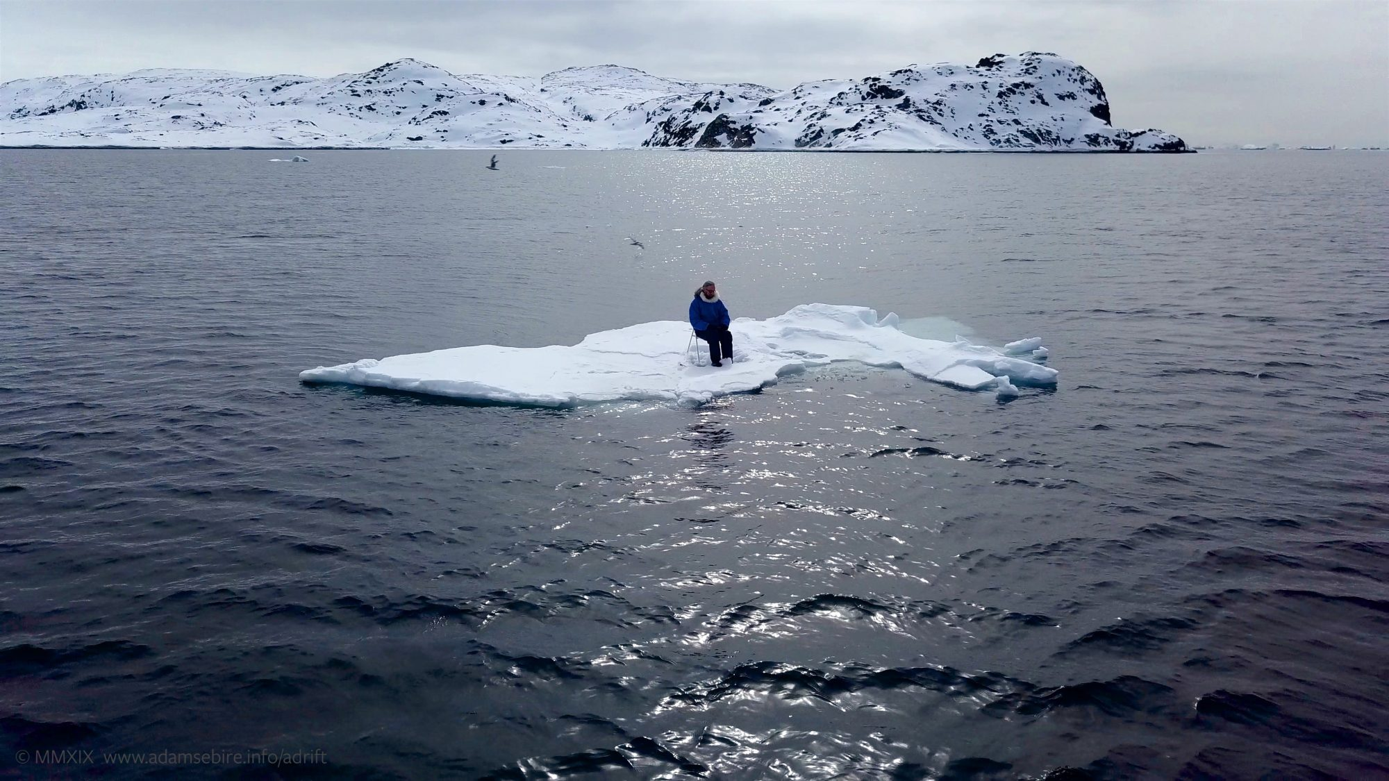 A white piece of ice floats in the Arctic sea, and a man sits in a chair i the middle of it.